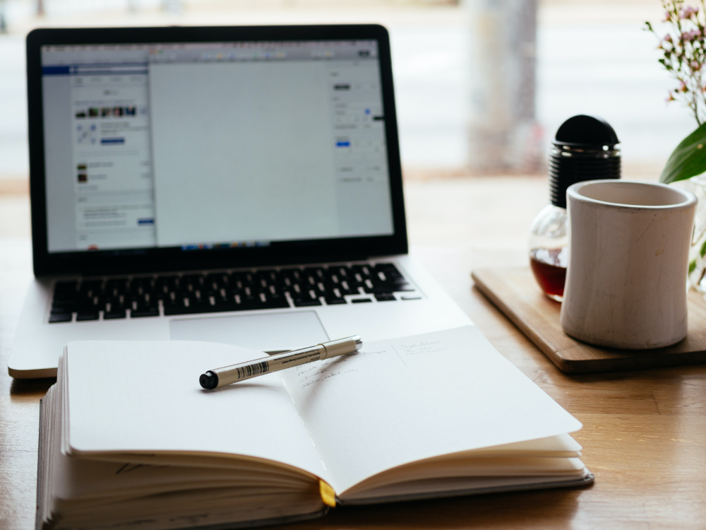 A laptop and an open book with a pen on a desk beside a mug